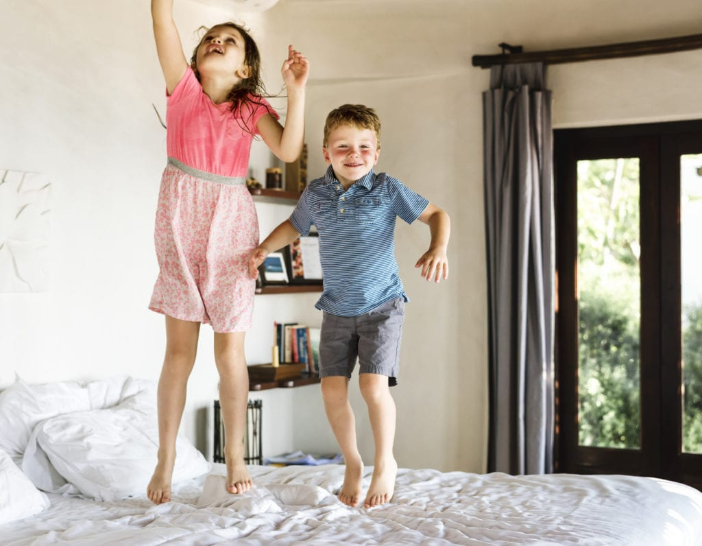 Kinder springen auf dem Bett